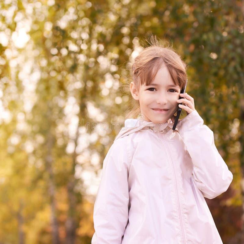 Joven feliz habla de celular roaming telefónico Personas con smartphone Fondo del otoño imagen de archivo