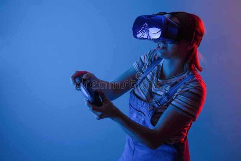Le vr de jeu La fille dans le casque et le contrôleur joue un jeu avec la lumière créative concept des sports de cyber gibiers vi image libre de droits
