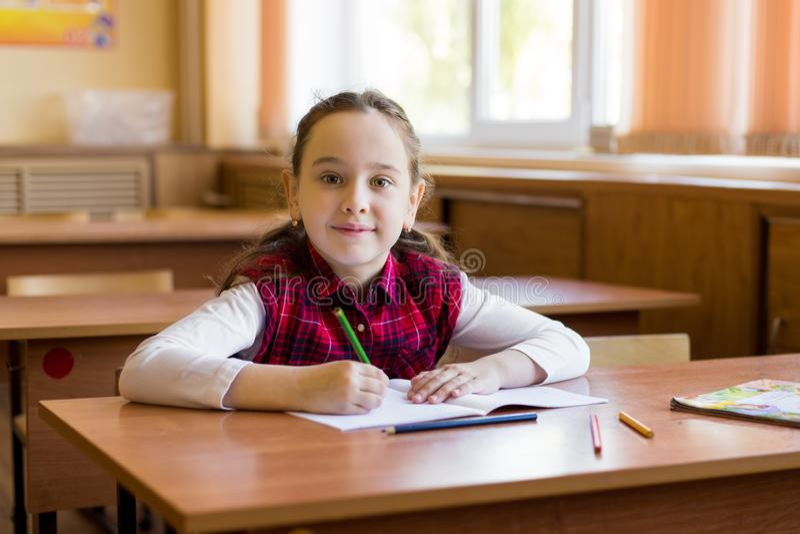 Lächelndes, kaukasisches Mädchen sitzt am Schreibtisch im Klassenzimmer und ist bereit zum Lernen Portrait der jungen Vorschuldne stockfotografie