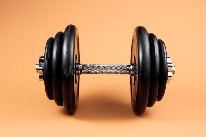 Tampon professionnel et assiettes de poids sur fond beige Clochette en métal noir avec poignée en argent chrome Gym photo libre de droits