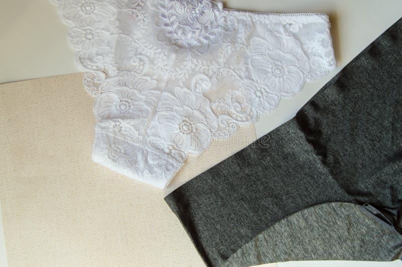 Fashionträttade underkläder Spetsa vita trosor kontra svart bekväm bikini Vackra satser att välja bland Plattor Kvinnor arkivfoton