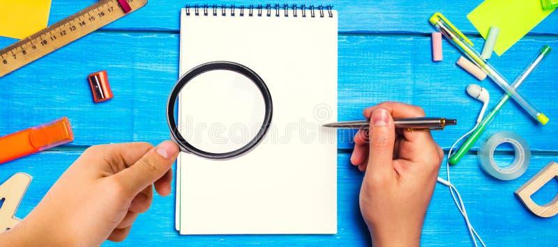 Schoolconcept, toebehoren de schooljongen wijst op een blocnote hand met vergrootglas nieuwe ideeën , huiswerkoplossing terug naa stock afbeelding