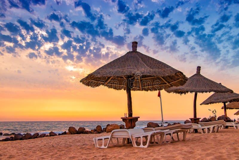 Doordenstoelen met umrellas op het strand met mooie zonsondergang in Senegal, Afrika Er is blauwe lucht en gouden en rode zon Het stock foto's