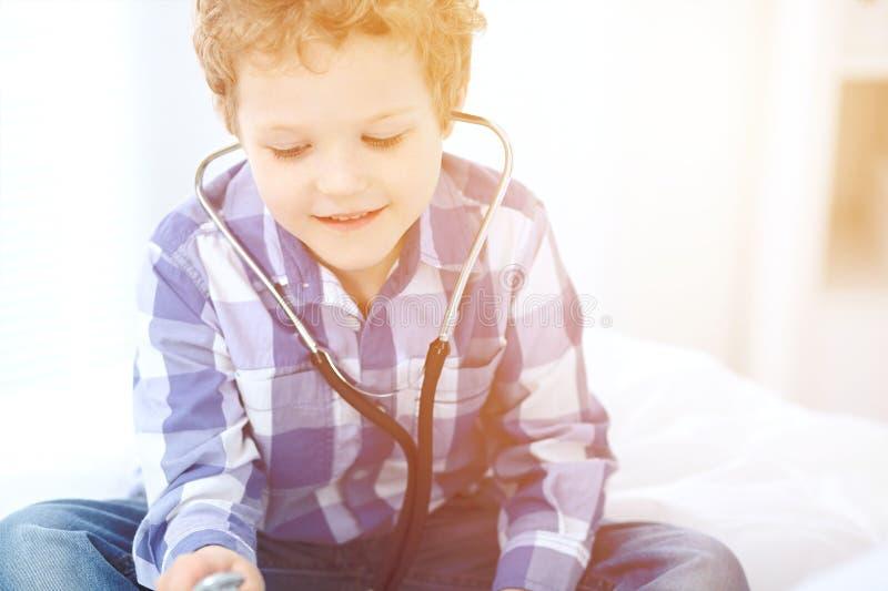 Médecin et enfant. Le petit garçon joue avec le stéthoscope tandis que le médecin communique avec lui. thérapie et images stock