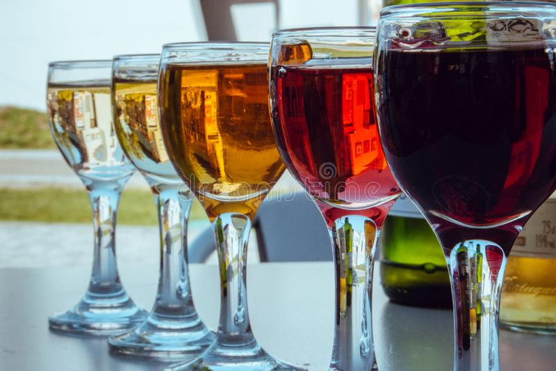 Fila di bicchieri da vino di piccole dimensioni con un vino diverso sbiadito Vasi bianchi, rosa e vino rosso Set di vini Concetto immagine stock