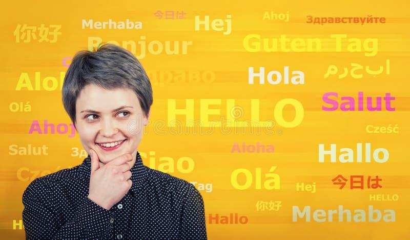 Fassen Sie hallo mit verschiedenen Übersetzungen auf der gelben Wand ab Mehrsprachige Frau, die viele Sprachen lernt und spricht  stockbilder