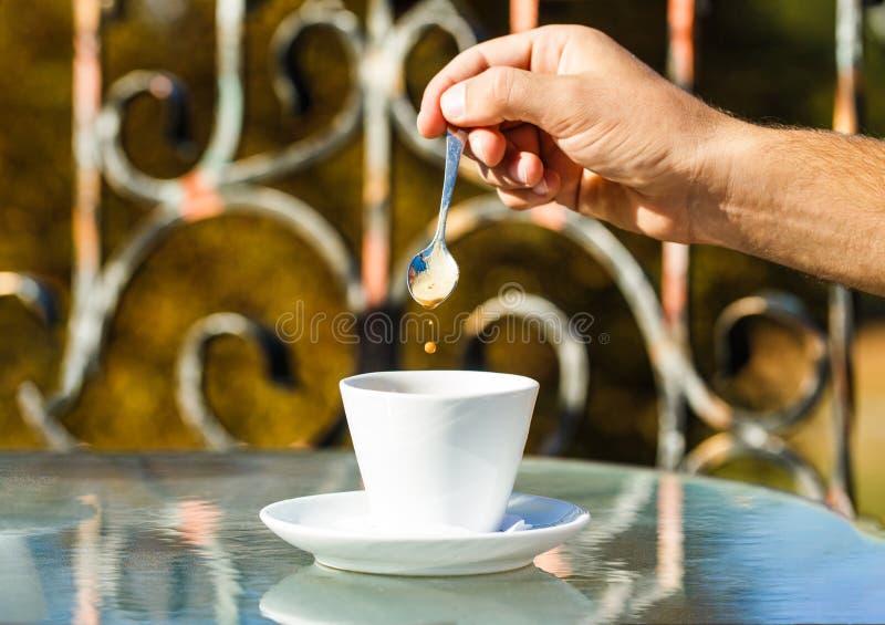 Ręka człowieka trzyma łyżkę do kawy lub kubek do kawy Kubek z kawy Cappuccino i czarnego espresso Napój kawowy Blisko mężczyzny zdjęcia royalty free