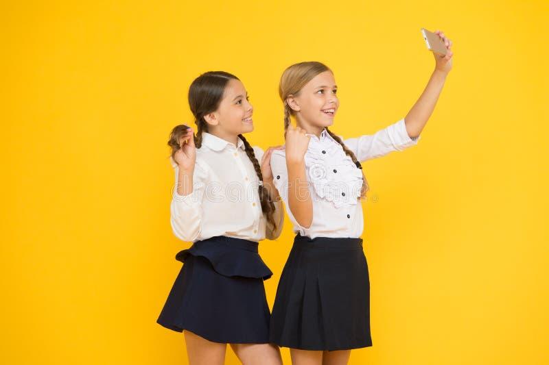 Voor mijn profiel de jonge geitjes maken selfie foto, vriendschap kleine meisjes in eenvormige school Terug naar School onderwijs stock afbeeldingen