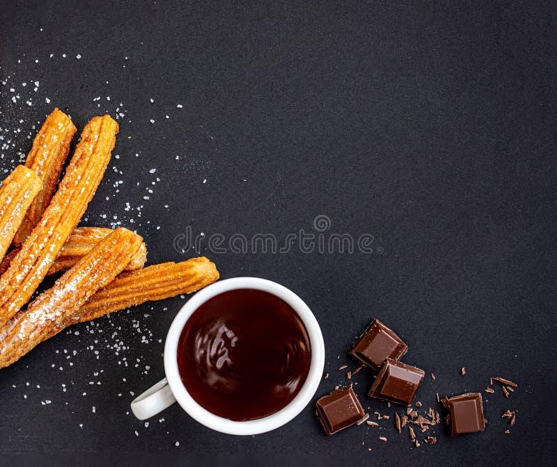 Churros mit flüssiger Schokolade Churro - gebratenes Teiggebäck mit Zuckerpulver auf schwarzem Hintergrund Kopieren Sie Platz lizenzfreies stockfoto