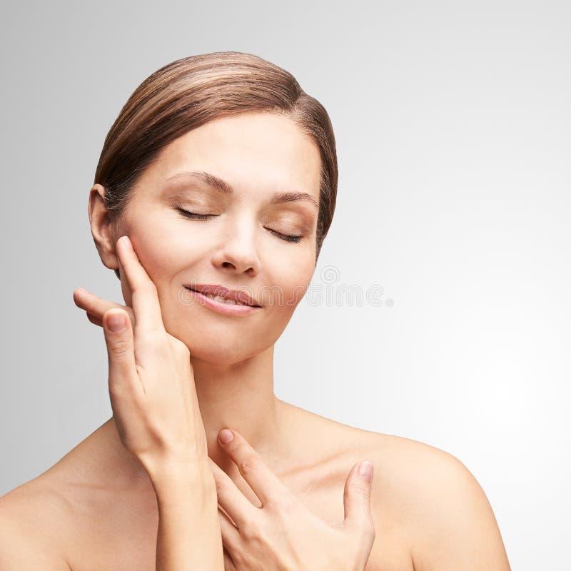 Natuurlijke schoonheidsportret met handen Cosmetologie, volwassen vrouw Cosmetische crème Huidverzorging Elegant meisje stock afbeelding