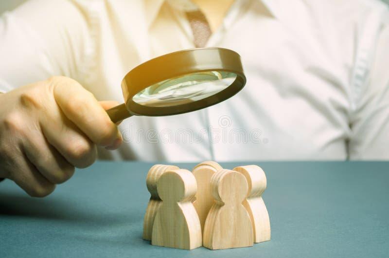 Företagsledare som håller ett förstoringsglas över ett arbetslag Begreppet att hitta nya anställda Teamliding Team royaltyfria foton