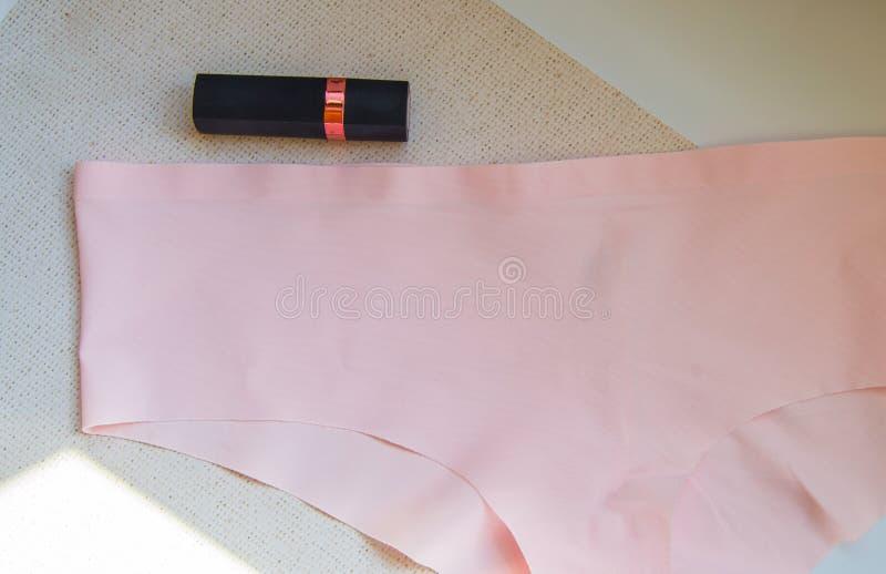 Accessoires pour femmes en laque plate - sous-vêtements et cosmétiques La vue du haut des culottes en bikini rose et rouge à lèvr photos libres de droits