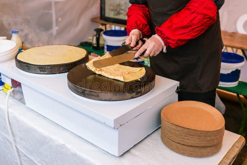 Un homme fait des crêpes sur un poêle électrique Ccrêpes farcies pour les vacances Cuisiner en préparant la nourriture dans la ru image stock