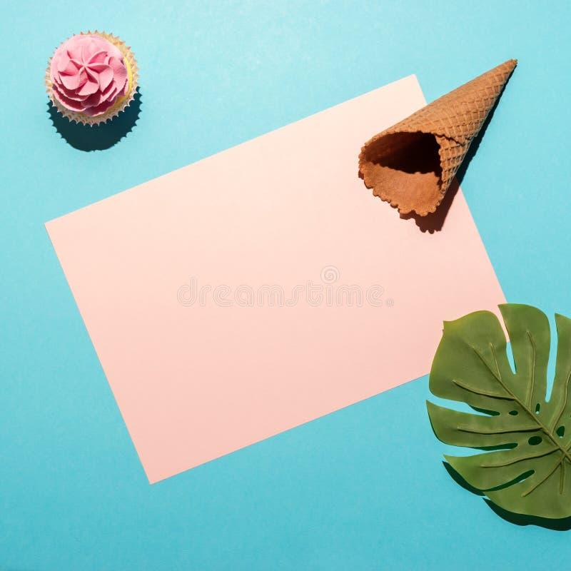 Tropiskt palmblad med cupkaka och glass på ljusblå bakgrund Minimal sommarsammansättning Plattor royaltyfri bild