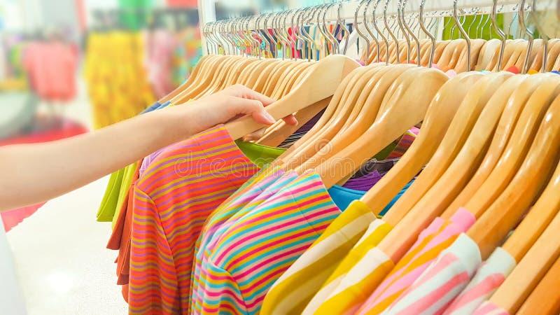 Acheter des vêtements dans un centre commercial Fermez la main d'une femme Choisir et réduire les T-shirts colorés sur un cintre  image libre de droits