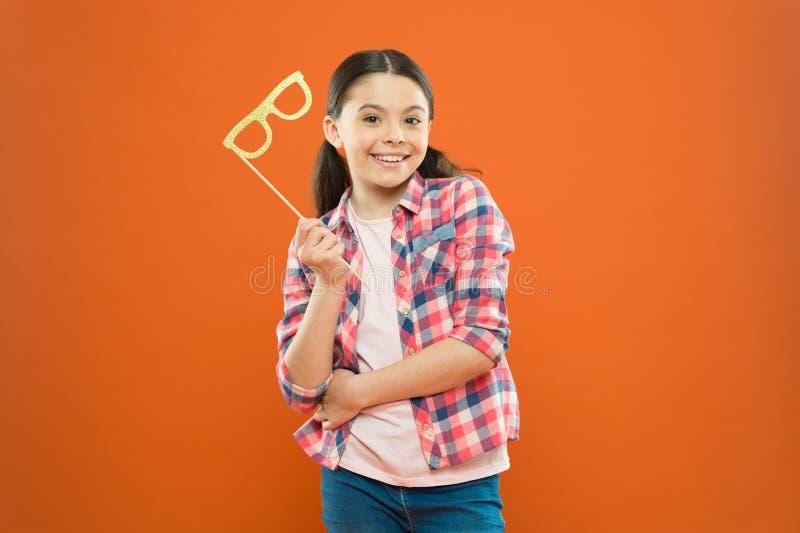 Mijn cabine van de partijfoto Vrolijk partijmeisje op oranje achtergrond Aanbiddelijke weinig partijsteunen van de kindholding op stock fotografie
