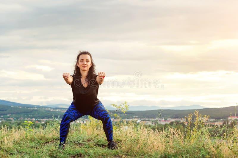 De jonge vrouw doet training bij aard Het meisje van de sportvrouw in openlucht Vrouwelijk fitness meisje die sportoefeningen in  royalty-vrije stock afbeeldingen