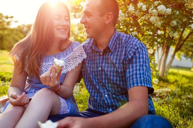 Jeunes couples mangeant de la glace et bavardant dehors. Femme et homme se refroidissant dans le jardin de printemps au coucher du photo libre de droits