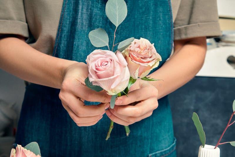 Imagem cortada da florista feminina no trabalho Arranjar várias flores em bouquet Feche as flores na mão Local de trabalho floris imagens de stock