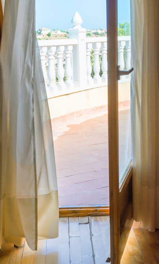 Öppna dörr med genomskinliga, vita gardiner med sikte på terrasbergarnas dal Blå himmelljus Medelhavet royaltyfri foto