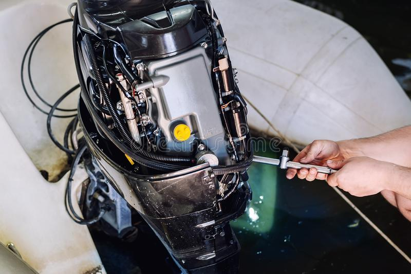 riparazione meccanica del motore gonfiabile a motoscafo nel garage Servizio stagionale e manutenzione del motore navale Motore de immagine stock