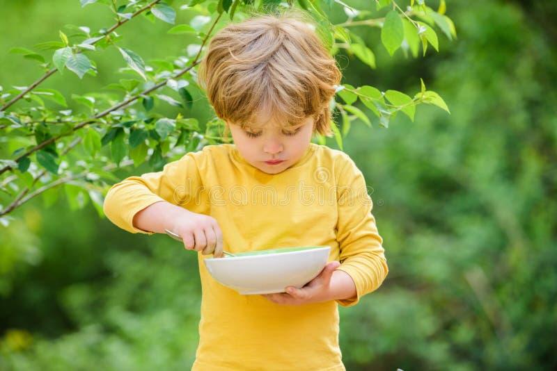 E r r N?ring f?r ungar Liten litet barnpojke att äta havregröt arkivfoto
