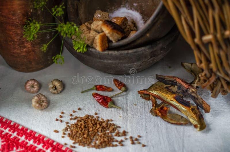 El proceso de la cocina rústica champiñones secos, trigo sarraceno, ajo, pimienta roja, migones de pan Cocina utensilios rústicos imagen de archivo libre de regalías