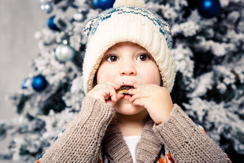Tema natalizio e bambini Un bambino caucasico con un cappello caldo e un maglione che posano, mangiano dolcezza, volto sporco Nat immagini stock
