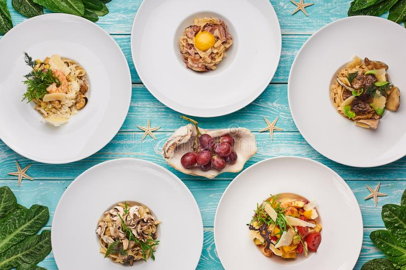 Ensemble de pâtes sur fond de bois bleu cuisine italienne plate Gastronomie Délicieux plats de restauration photo stock