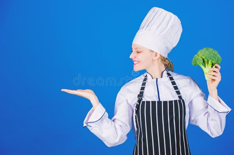 E r o Овощ владением девушки Органическое питание Брокколи владением шеф-повара женщины указывая на стоковые изображения rf