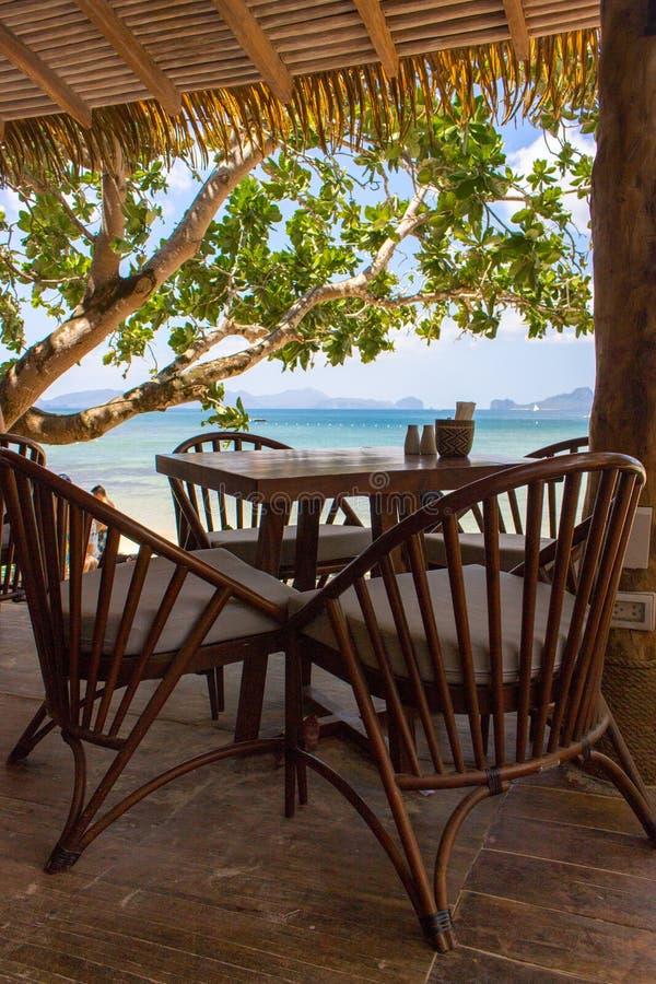 热带海滩树下空桌椅 海景海滩咖啡馆 户外餐厅木家具 图库摄影