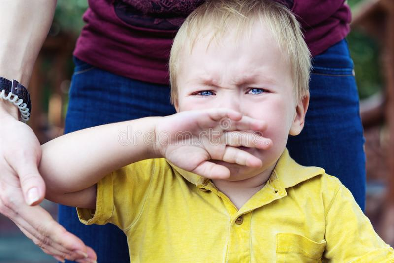 Un niñito con una camiseta amarilla está llorando y cubriéndose la boca con la mano. Realmente molesto Lágrimas en su mejilla fotografía de archivo
