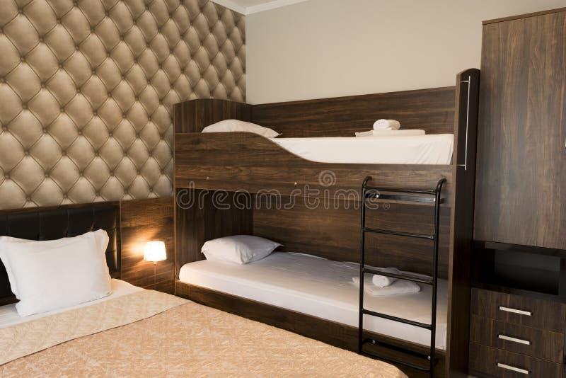 古典酒店卧室内部设计 大床、双层床 带棕色色调家具的家庭室 图库摄影
