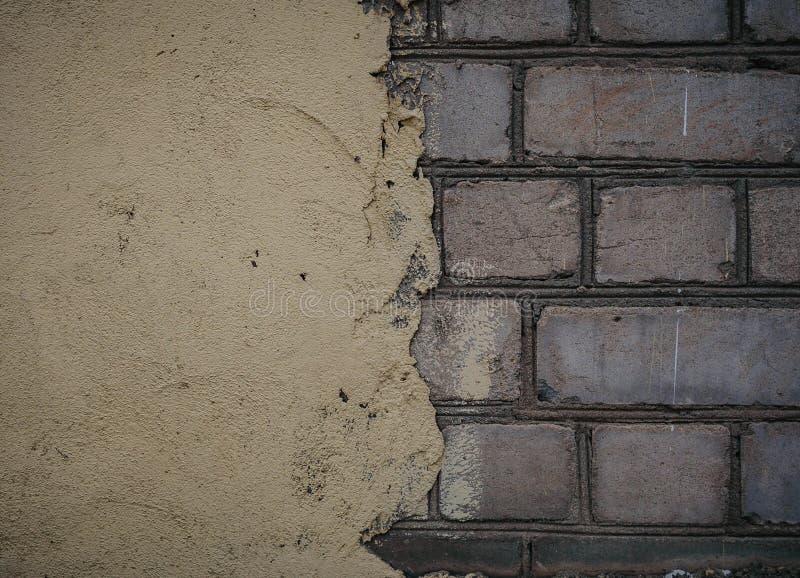 混凝土墙下的红砖 纹理表面 半彩墙 背景 裂纹和粗糙度 免版税库存照片