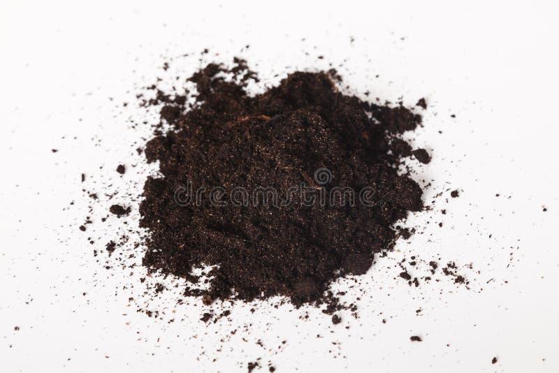 Pile di terra fertile nero su fondo bianco Sollevamento di sporco su fondo bianco Concetto della giornata mondiale del suolo fotografia stock libera da diritti