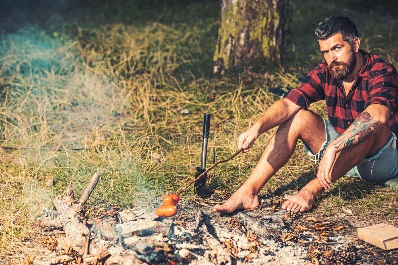 Un vagabondo accampato nei boschi Un tipo che frigge salsicce per incendio Uomo a piedi nudi seduto sull'erba nella foresta immagine stock