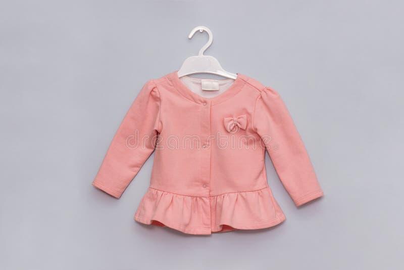 Meisje gestileerd uiterlijk Pastel roze elegante jas op hanger op grijze wandachtergrond Moederkleding voor vrouwelijke kinderen stock afbeeldingen