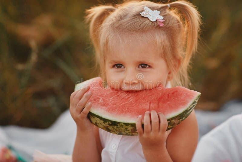 花园里吃西瓜的孩子 小女孩拿着一片西瓜在花园里玩耍 童园 库存图片