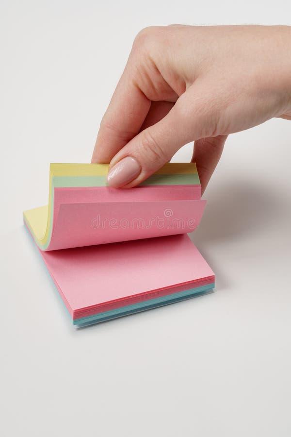 Ensemble de papier de note vierge de différentes couleurs Collecte de notes collantes sur fond gris Feuillage à la main par le pa images stock