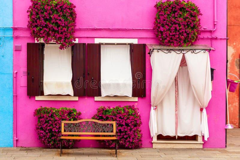 Розовый дом с розовыми цветами и растениями Хорошая скамья под окнами Красочный дом на острове Бурано недалеко от Венеции, Италия стоковая фотография rf
