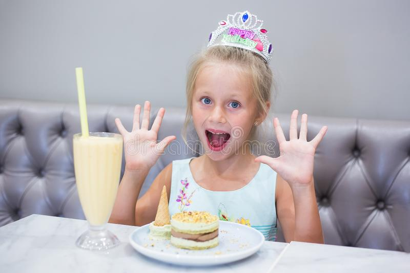 A garota numa festa de aniversário Felicidades alegres e alegres de menina Coquetel e bolo sobre a mesa foto de stock royalty free