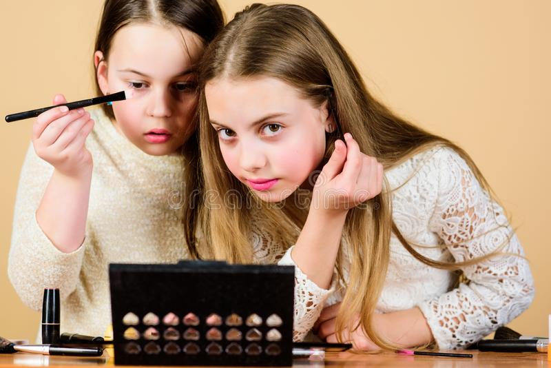Деление макияжа, подчеркивающее красоту моделей Мелкие макияжисты Маленькие девочки рисуют лицо и делают стоковая фотография