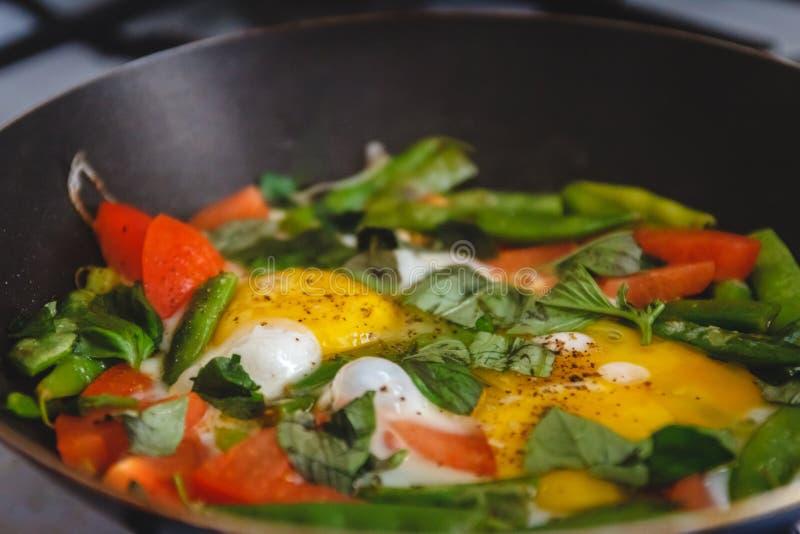 煎鸡蛋,在锅里放蔬菜和香草,在火上,在炉子上,做饭 顶视图,特写 概念,健康早餐 库存照片