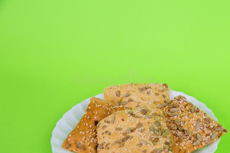 在绿色背景的自创蜂 酥脆面包用向日葵、胡麻和芝麻 r 库存照片