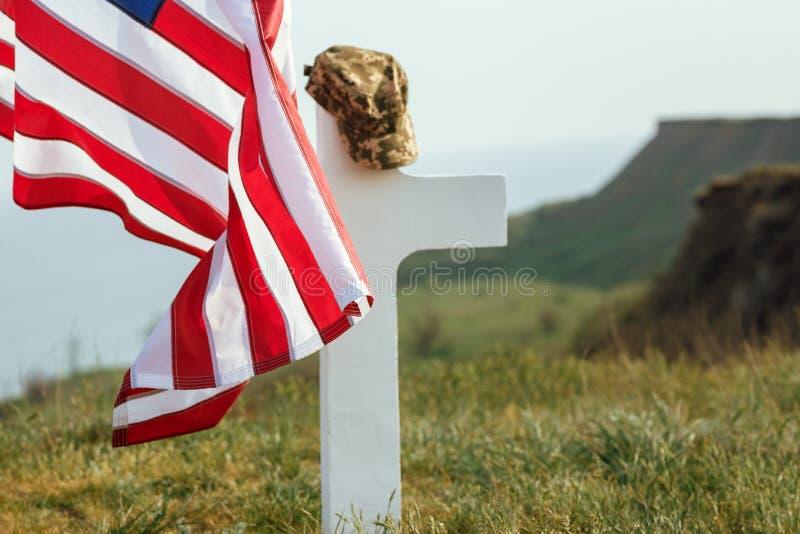 En soldats grav Den amerikanske flaggan över den avlidne soldatens grav Vid graven ett militärt tak royaltyfri foto