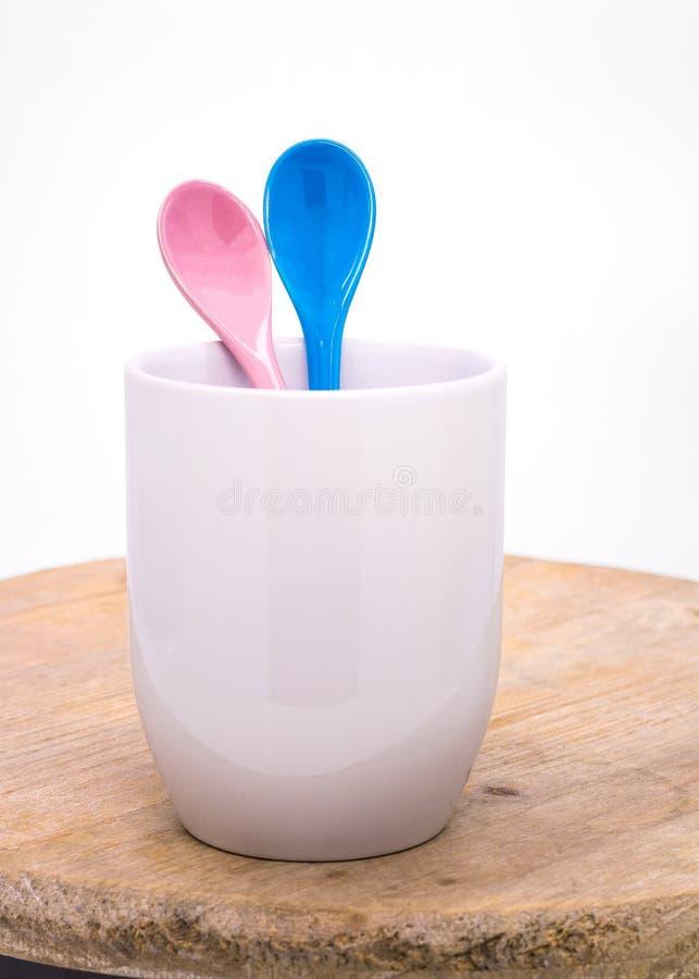 颜色在杯子的陶瓷匙子在木背景 五颜六色的概念 免版税库存照片