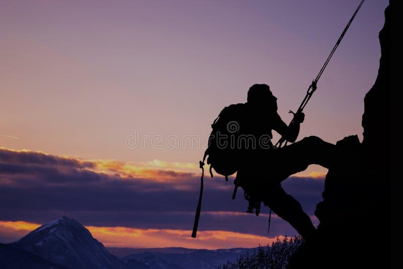 在年轻mountainer的侧视图 现出轮廓在行动的mountainer 免版税库存图片