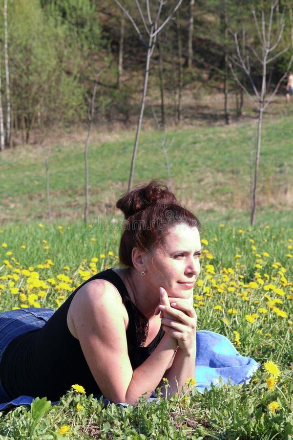 A garota está descansando no campo de primavera Mentiras na cama Os dentes-de-leão estão florescendo, a grama está crescendo foto de stock royalty free