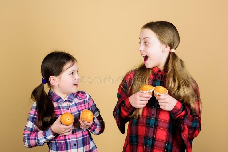 Wir alle lieben Desserts Kleine Kinder, die glücklich lächeln mit Kuchen Nachtisch in Händen Gute kleine Mädchen essen gerne lizenzfreie stockbilder
