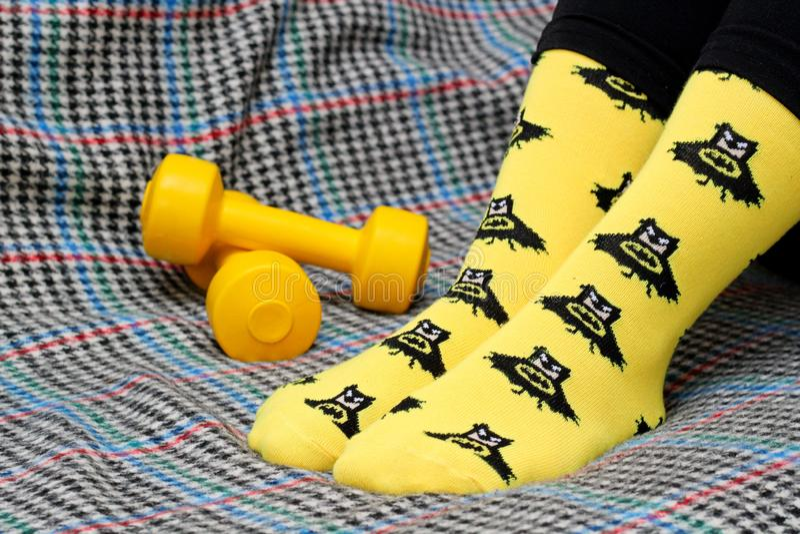 Девушка, сидящая на диване Желтые носки с черным изображением Бэтмена Змеи Вид сбоку стоковые фотографии rf
